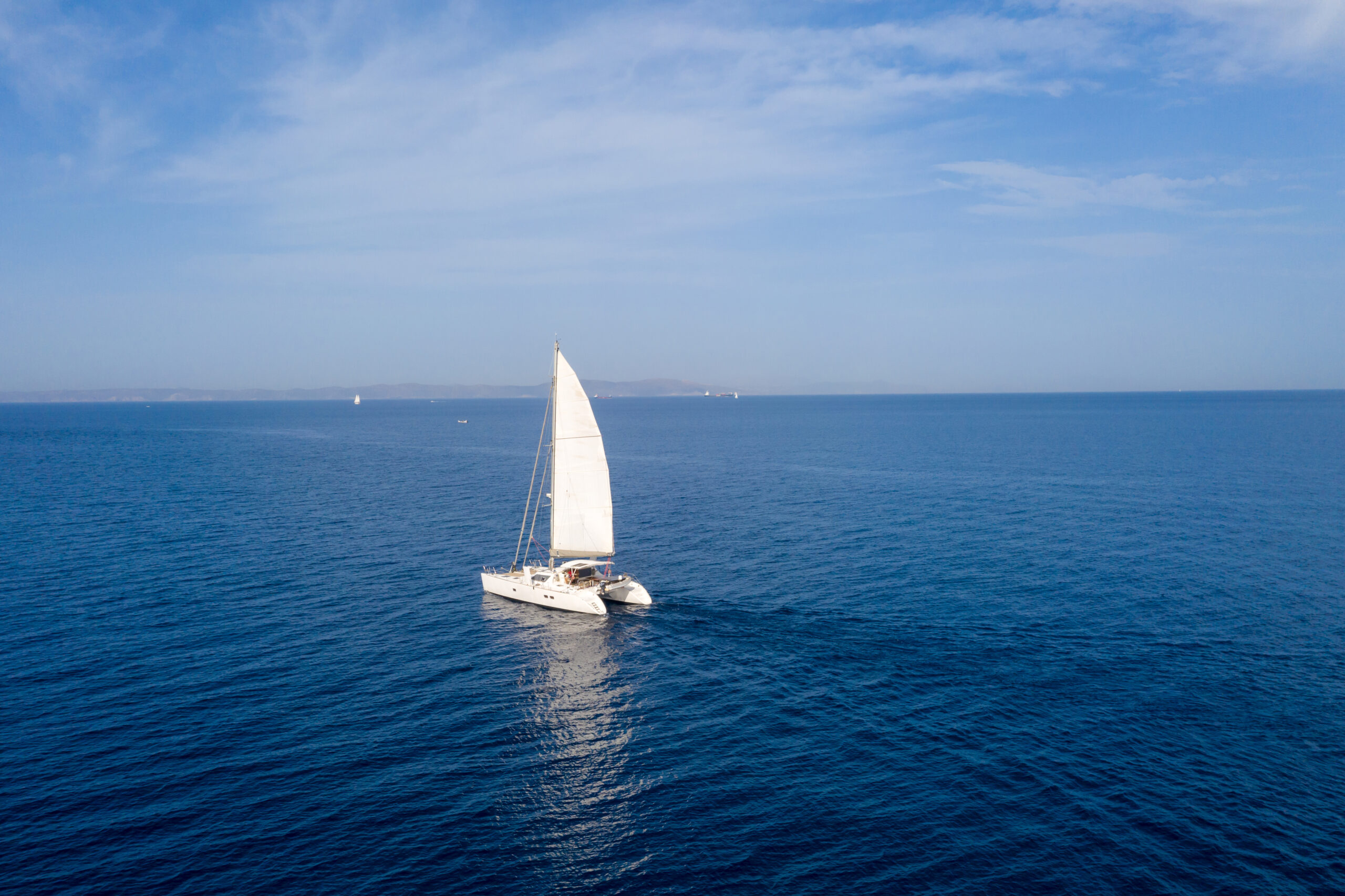 Sailing. Sailboat catamaran with white sails, cloudy sky and rippled sea background. Summer holidays in Aegean sea Greece