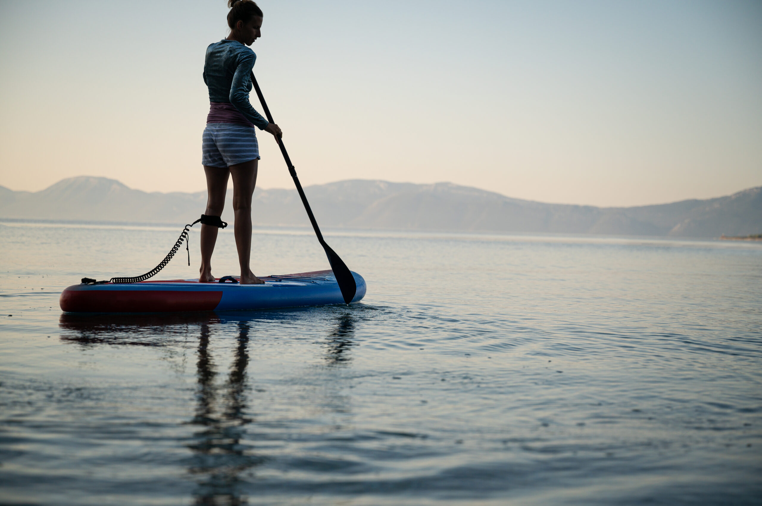 Low angle view of young woman exercising early in the morning, paddling on sup board floating on calm sea water.